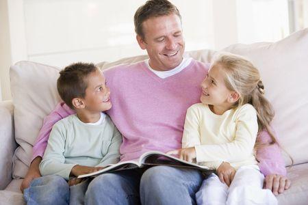 bambini seduti: Uomo e due bambini seduti nel salotto di lettura libro e sorridente Archivio Fotografico