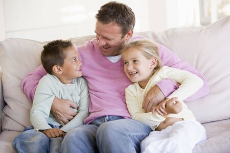 Man and two children sitting in living room smiling Stock Photo - 3602931