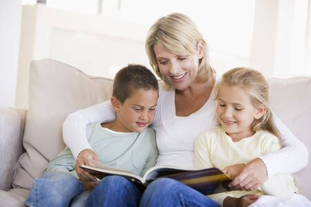 Woman and two children sitting in living room reading book and smiling Stock Photo - 3601292