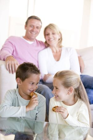 Family sitting in living room eating cookies and smiling Stock Photo - 3601281
