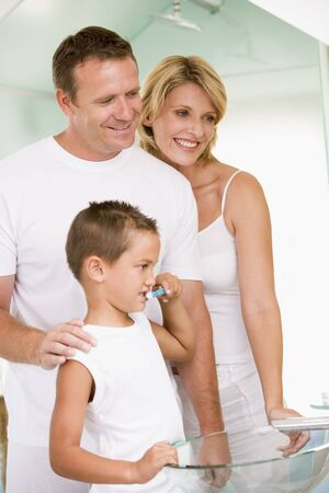 Couple in bathroom with young boy brushing teeth photo