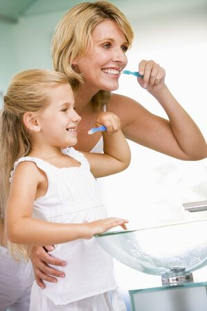 Woman and young girl in bathroom brushing teeth Stock Photo - 3601023