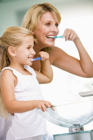 Woman and young girl in bathroom brushing teeth photo