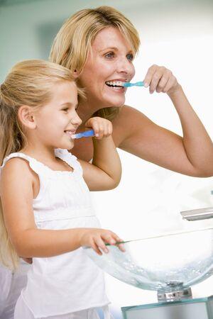 Woman and young girl in bathroom brushing teeth Stock Photo - 3600748