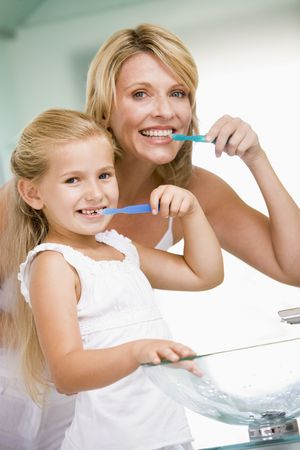 hygeine: Woman and young girl in bathroom brushing teeth Stock Photo