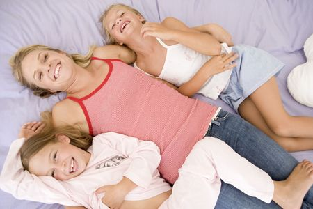 Woman and two young girls lying in bed playing and smiling Stock Photo - 3603275