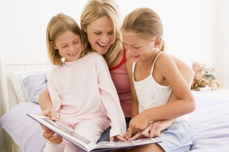 Woman and two young girls in bedroom reading book and smiling photo