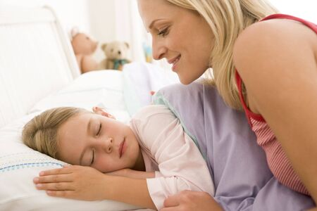 Woman waking young girl in bed smiling photo