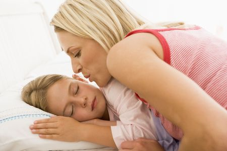 Woman waking young girl in bed with a kiss photo