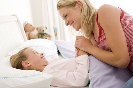Woman with young girl in bed smiling Stock Photo - 3601262