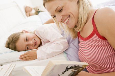 mujer leyendo libro: Mujer libro de lectura a la ni�a en la cama sonriendo