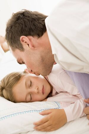 Man waking young girl in bed with kiss photo