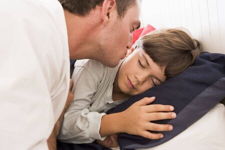 Man waking young boy in bed with kiss photo