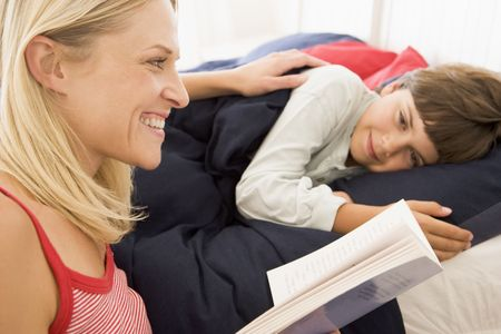 Woman reading book to young boy in bed smiling photo