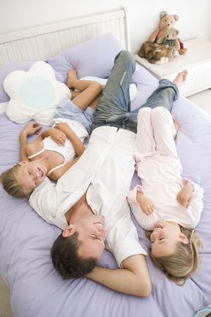 Man lying in bed with two young girls smiling Stock Photo - 3601306