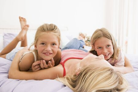 Woman lying in bed with two young girls smiling photo