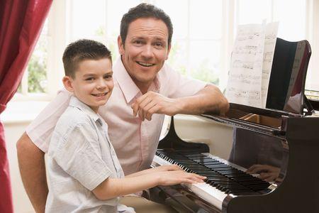 tocando piano: El hombre y la joven tocando el piano y sonriente