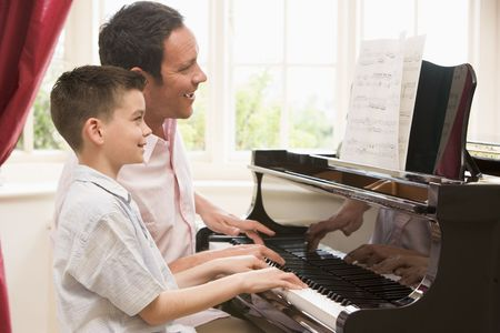 grand sons: Man and young boy playing piano and smiling