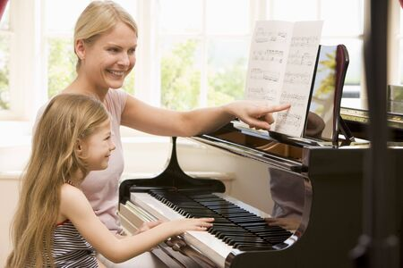 teaching adult: Woman and young girl playing piano and smiling Stock Photo