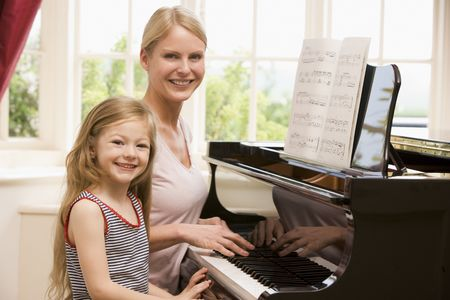 Woman and young girl playing piano and smiling photo