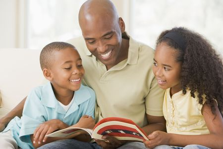 Man and two children sitting in living room reading book and smiling Stock Photo - 3603743