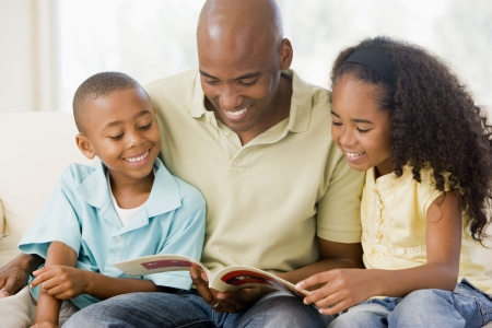 reading room: Man and two children sitting in living room reading book and smiling