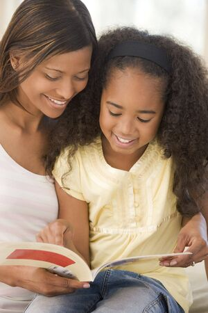 Woman and young girl sitting in living room reading book and smiling photo