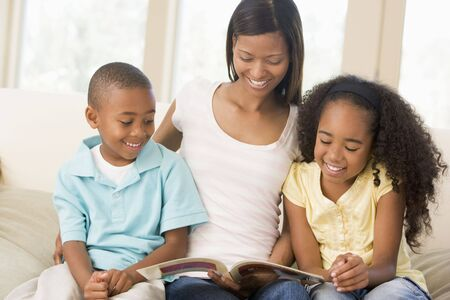 Woman and two children sitting in living room reading book and smiling Stock Photo - 3602831