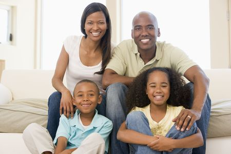 Family sitting in living room smiling Stock Photo - 3603001