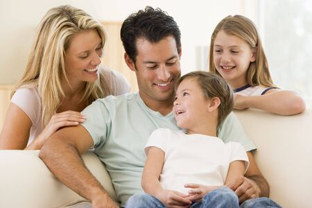 Family sitting in living room smiling Stock Photo - 3602899