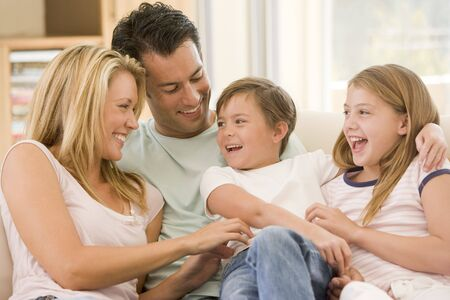 family on couch: Family sitting in living room smiling