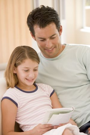Man and young girl in living room reading book and smiling Stock Photo - 3600824