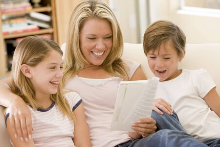 Woman and two young children in living room reading book and smiling photo