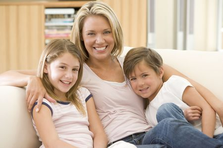 Woman and two young children in living room smiling Stock Photo - 3601491