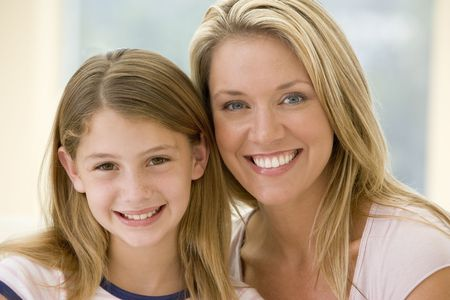 Woman and young girl in living room smiling photo