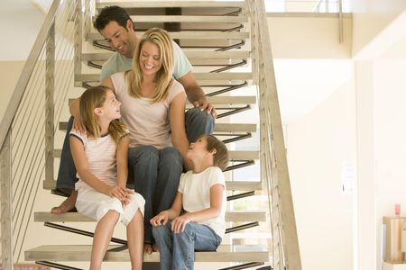 Family sitting on staircase smiling photo