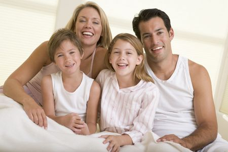 Family sitting in bed smiling photo