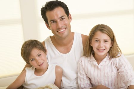 Man with two young children sitting in bed smiling photo