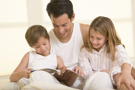 Man with two young children sitting in bed reading a book and smiling photo
