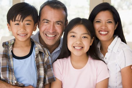 mixed family: Family in living room smiling Stock Photo