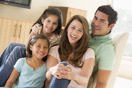 indoor: Family sitting in living room smiling