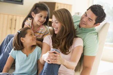 Family sitting in living room smiling Stock Photo - 3603443