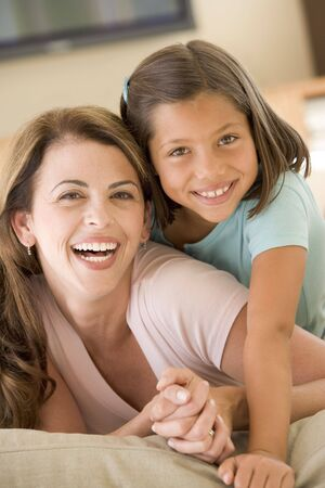Woman and young girl in living room smiling Stock Photo - 3602972