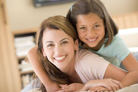 daughter mother: Woman and young girl in living room smiling Stock Photo