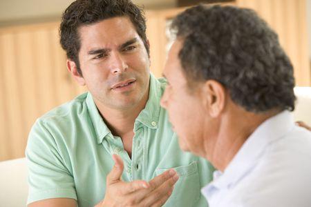deux personnes qui parlent: Deux hommes dans le salon en faisant valoir Banque d'images