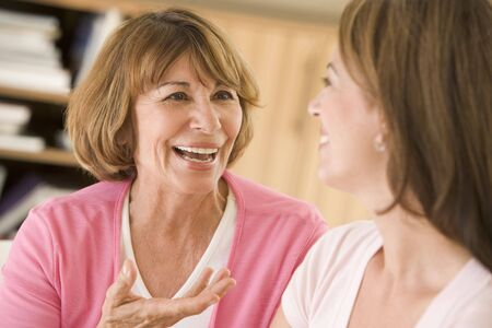 women talking: Two women sitting in living room talking and smiling
