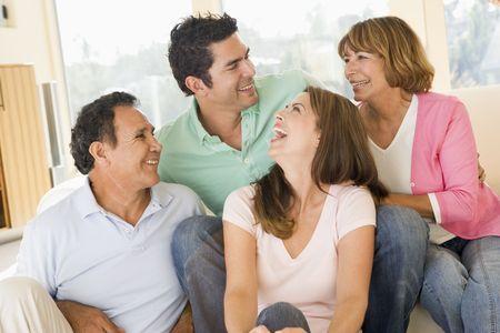 padres hablando con hijos: Dos parejas sentados en la sala sonriendo y riendo Foto de archivo