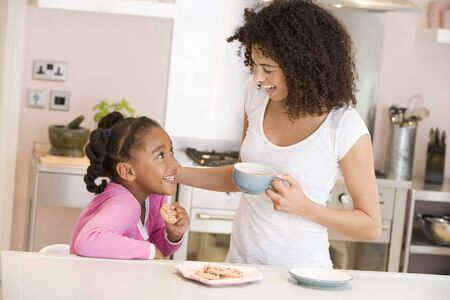 african american mother and daughter: Woman and young girl in kitchen with cookies and coffee smiling Stock Photo