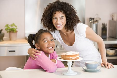Woman and young girl in kitchen with cake and coffee smiling photo