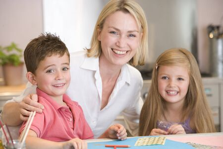 Woman and two young children in kitchen with art project smiling photo